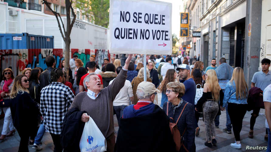 "Martin Sagrera, 83, Catalonian retiree living in Madrid, holds a sign that reads ""Don't complain if you don't vote"" ahead of the April 28 Spanish general election, in downtown Madrid, April 27, 2019."