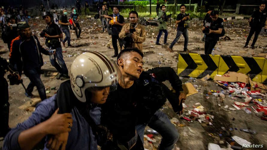 An injured police officer leaves the area with the help of his colleagues after clashes with protesters in Jakarta, Indonesia, early May 23, 2019.