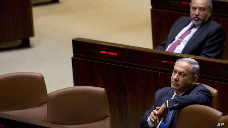 FILE - Israeli Prime Minister Benjamin Netanyahu and former Israeli defense minister Avigdor Liberman sit in the Knesset, Israel's parliament, in Jerusalem, May 23, 2016.