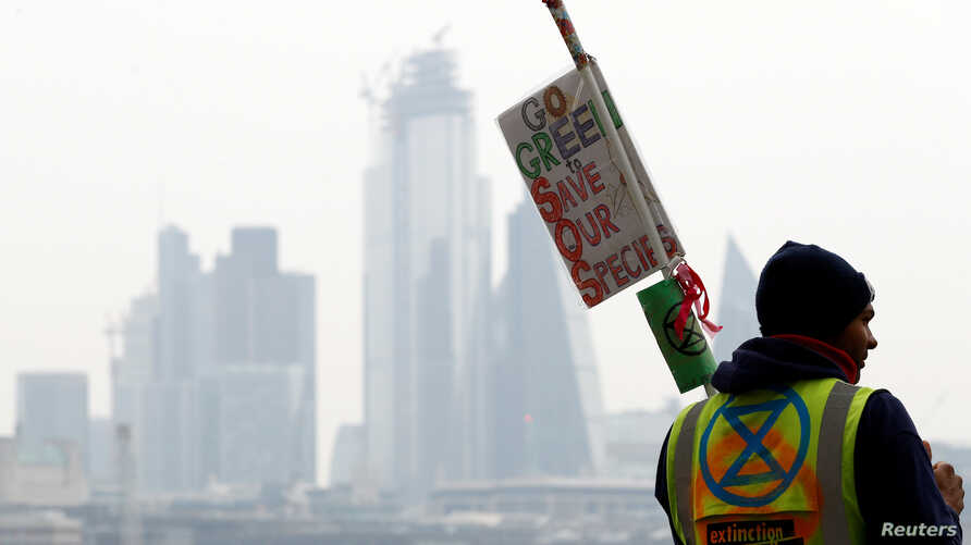 FILE - A climate change activist holds a placard at Waterloo Bridge during the Extinction Rebellion protest in London, Britain, April 16, 2019.