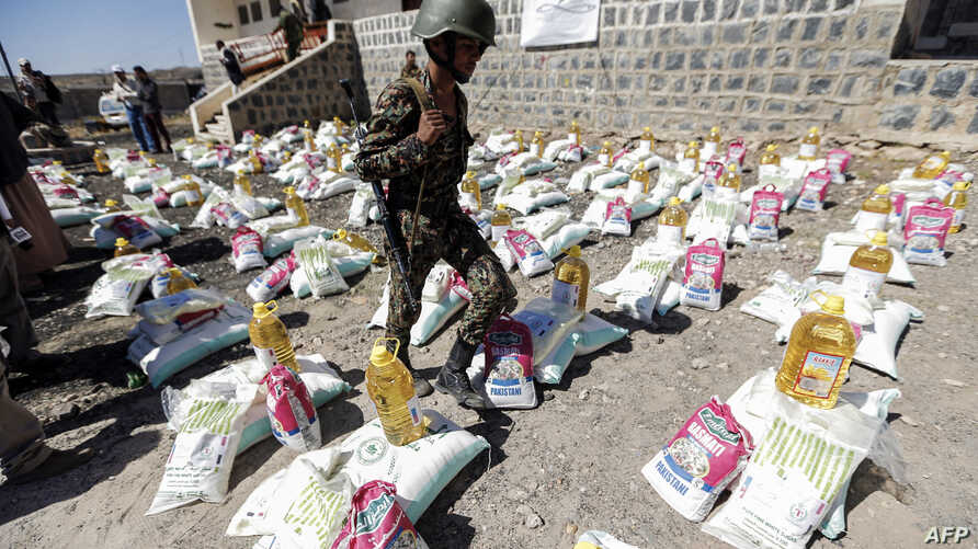 A Yemeni soldier, loyal to the Shiite Houthi movement, walks next to humanitarian aid supplies given by the Russian humanitarian relief mission in a camp on the outskirts of the capital Sanaa on March 16, 2017.