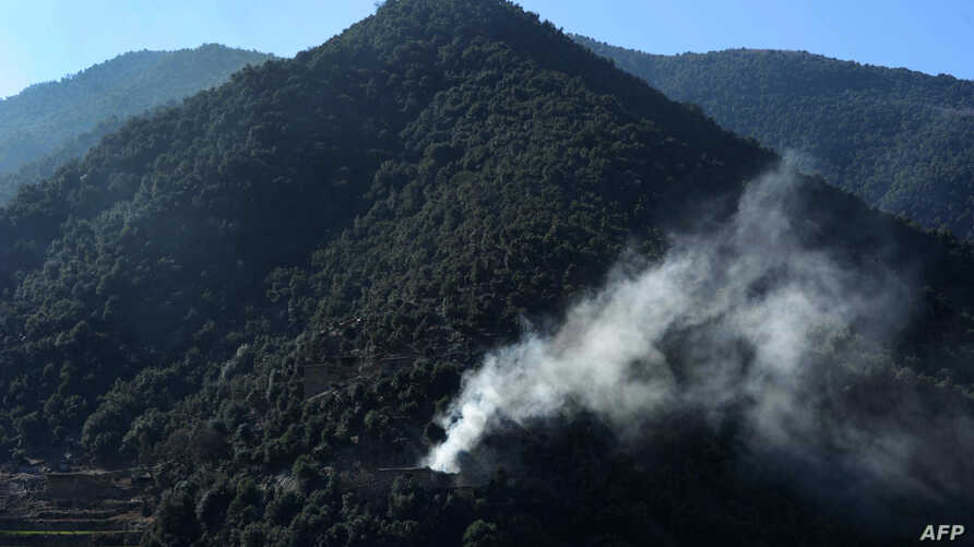FILE - Smoke rises from a hillside in Dangam district in Afghanistan's eastern Kunar province, Jan. 17, 2015.