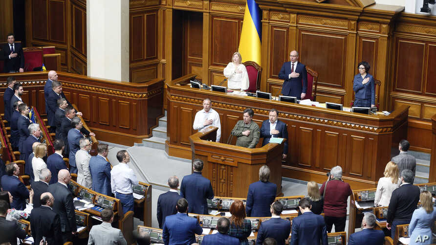 Ukrainian lawmakers sing the national anthem after a vote, in parliament, in Kiev, Ukraine,Thursday, April 25, 2019.