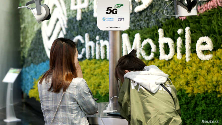 Customers are seen at a China Mobile flagship store displaying smart home experience with 5G network, in Shanghai, China, March 10, 2019.