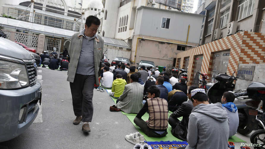 FILE - A Chinese man looks at Uighur people as they pray at a mosque in Shanghai, April 11, 2014.