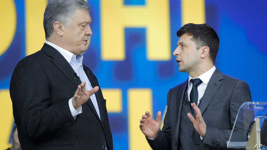Ukrainian President Petro Poroshenko, left, and Ukrainian presidential candidate and popular comedian Volodymyr Zelenskiy, right, argue during their debates at the Olympic stadium in Kiev, Ukraine, April 19, 2019.