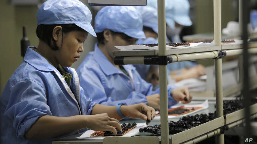 FILE - Chinese women work at a technology factory in southern China.