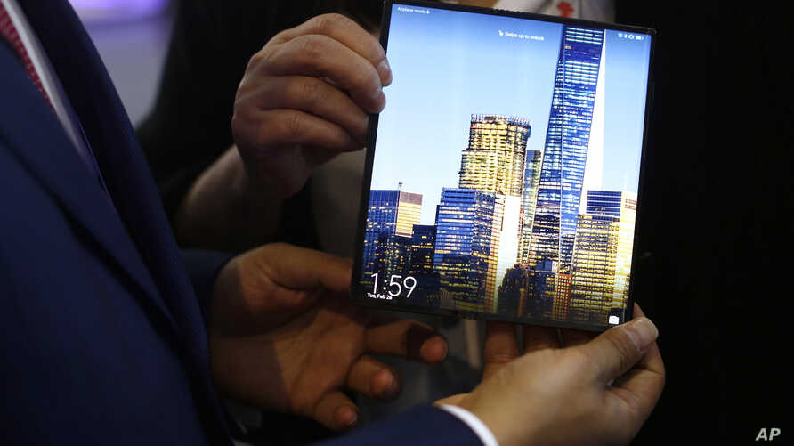 FILE - A man holds a new Huawei Mate X foldable 5G smartphone during the Mobile World Congress wireless show, in Barcelona, Spain, Feb. 26, 2019.