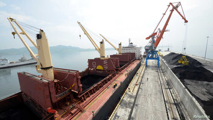 FILE - A cargo ship is loaded with coal at the North Korean port of Rajin, July 18, 2014.