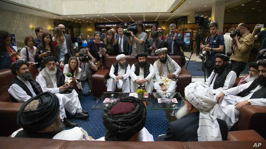 Mullah Abdul Ghani Baradar, the Taliban group's top political leader, left, Sher Mohammad Abbas Stanikzai, the Taliban's chief negotiator, second left, and other members of the Taliban delegation speak to reporters prior to their talks in Moscow, Rus...