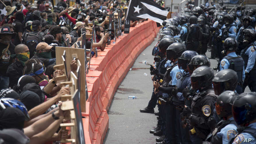 Demonstrators holding wooden shields are confronted by police during a protest against the Federal Fiscal Control Board, as part of the May Day celebration, in San Juan, Puerto Rico, May 1, 2019.