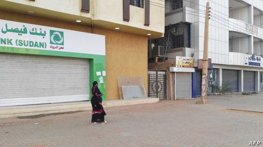 A Sudanese woman walks past two closed banks in a deserted street in Sudan's capital Khartoum on June 4, 2019.