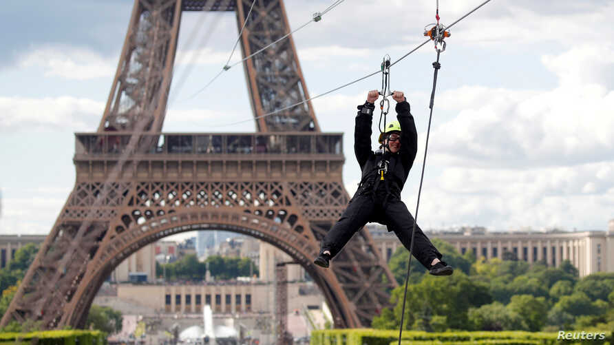 A participant rides a zipline from the second floor of the Eiffel Tower in Paris, France, May 28, 2019.