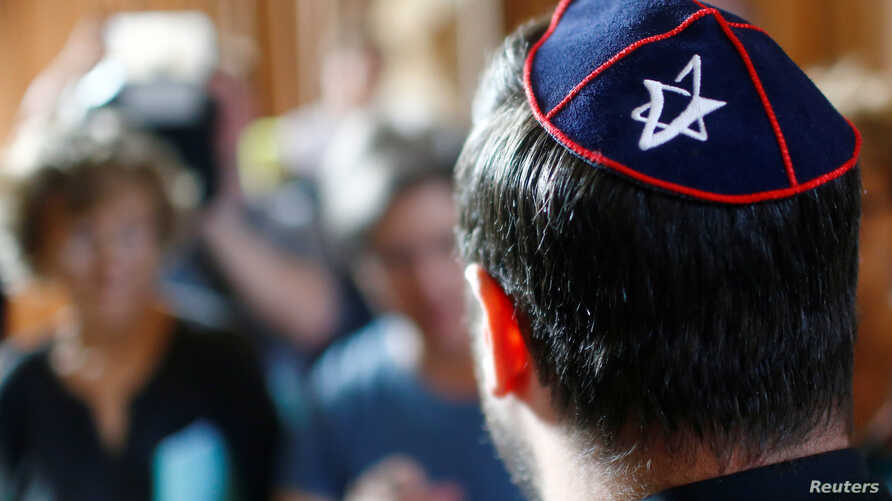 A member of Jewish community wearing a kippah talks to the media before the trial of a Syrian charged with assault at the Moabit court in Berlin, June 19, 2018.
