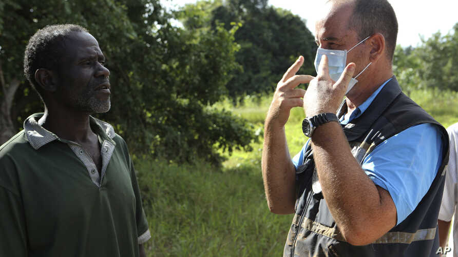 In this April 4, 2019 photo, Stephen Fonseca, right, gives a community leader guidance on handling the dead in Magaru, Mozambique.
