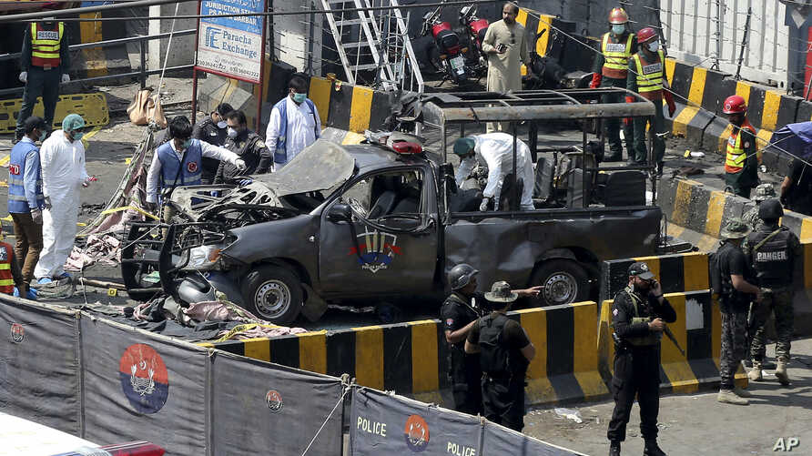 Pakistani security personnel surround a damaged police van in Lahore, Pakistan, Wednesday, May 8, 2019.