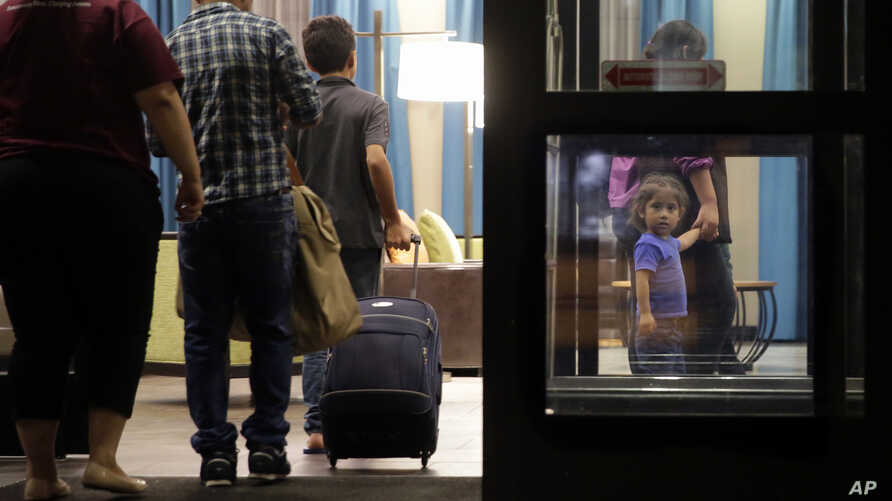 Immigrants seeking asylum who were recently reunited arrive at a hotel, in San Antonio, July 23, 2018. A federal judge says he will give the Trump administration six months to identify children who were separated from their families at the U.S.-Mexic...