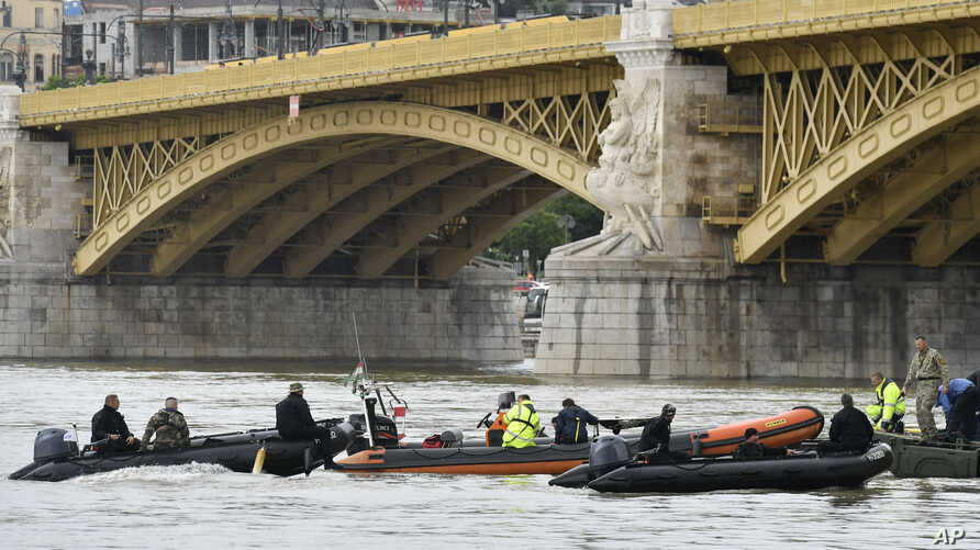 Rescuers in boats work to prepare to recover a capsized boat under Margaret Bridge in Budapest, Hungary, May 30, 2019.
