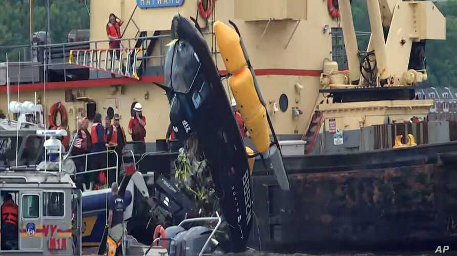 In this image made from video, a crane lifts a helicopter out of the water after it crashed into the Hudson River, May. 15, 2019. in New York. The 34-year-old pilot suffered just a minor hand injury after the hard splashdown. There were no passengers...