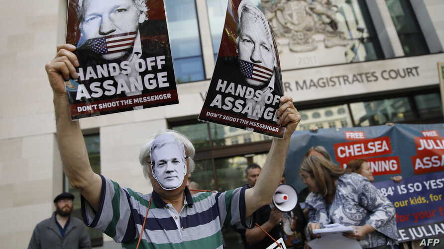 Supporters of WikiLeaks founder Julian Assange hold placards and a banners in protest outside Westminster Magistrates Court in London on May 30, 2019.
