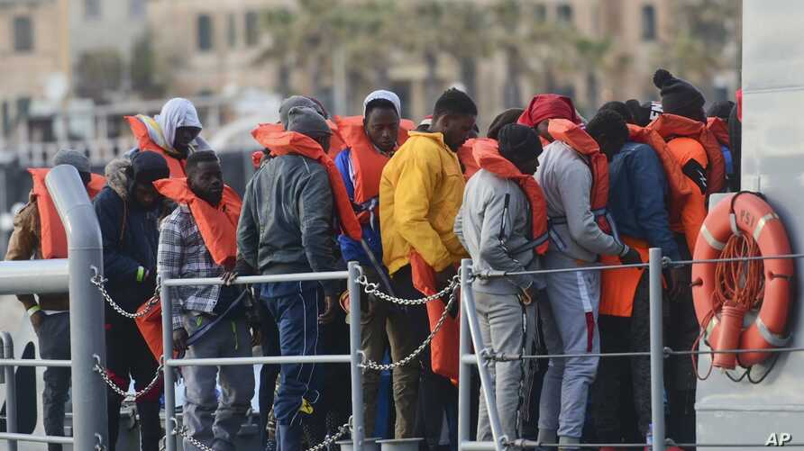 Migrants disembark after being transferred to Maltese army boats at sea and brought to Valletta harbor, Malta, April 13, 2019. Two Maltese soldier are being questioned in an attack that left one migrant dead and two wounded.