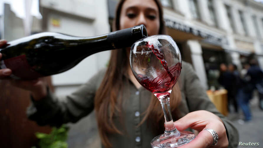 A shop assistant pours wine during a wine festival in Tbilisi, Georgia, Oct. 15, 2017.