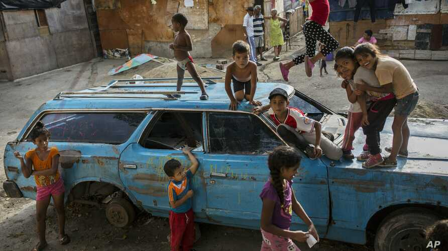 "Children play on top of an abandoned car at the ""Aguerridos Liberator"" shanty town in Caracas, Venezuela, Thursday, May 9, 2019. In the fourth month of their standoff, Venezuela's President Nicolas Maduro and opposition leader Juan Guaidó are unable to deliver a knock-out blow as Venezuela spirals deeper into neglect, isolation and desperation. (AP Photo/Rodrigo Abd)"