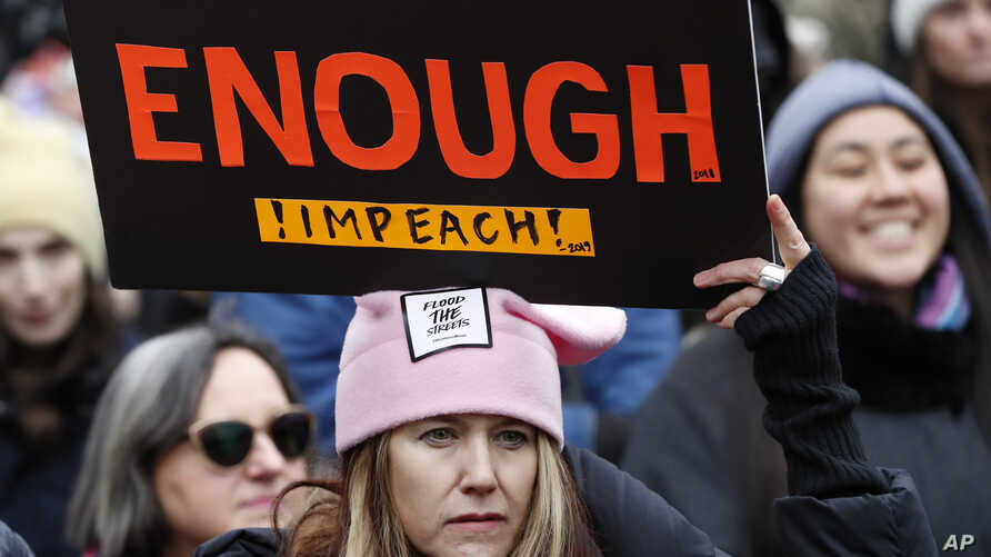 FILE - A woman holds a sign expressing her opinion about impeaching President Donald Trump at a rally organized by Women's March NYC at Foley Square in Lower Manhattan, Jan. 19, 2019, in New York.