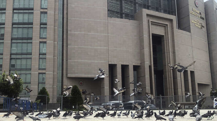 FILE - Pigeons fly outside the main Justice Palace in Istanbul, May 15, 2019, as the trial begins against Metin Topuz, a Turkish employee of the United States Consulate in Istanbul charged with espionage and attempting to overthrow the Turkish govern...