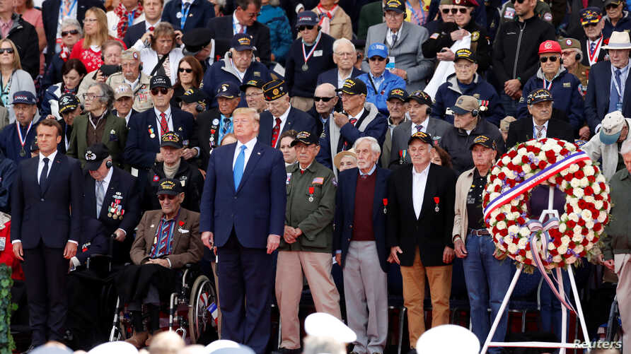 French President Emmanuel Macron and U.S President Donald Trump stand during a ceremony to mark the 75th anniversary of the D-Day at the Normandy American Cemetery and Memorial in Colleville-sur-Mer, France, June 6, 2019.