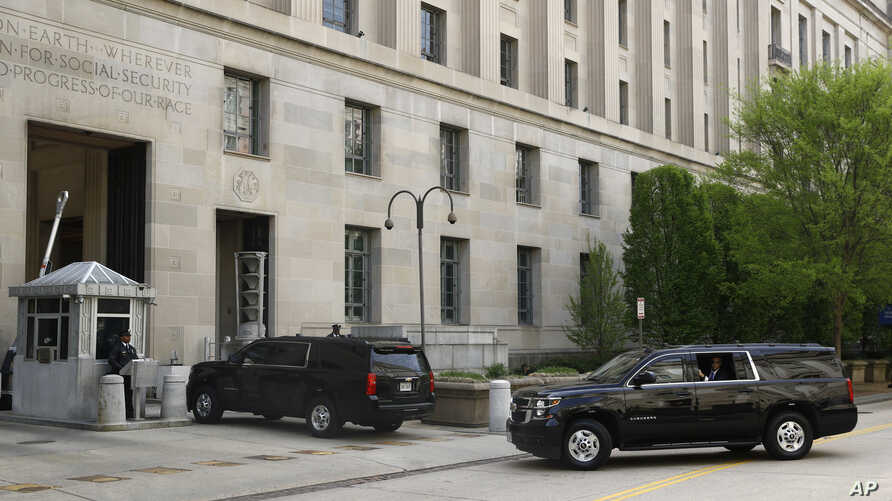 A motorcade for Attorney General William Barr arrives at the Department of Justice, April 17, 2019, in Washington.