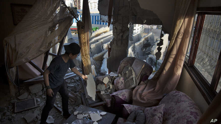A Palestinian boy cleans a sofa from the rubble of the partial damage on his family house after an Israeli airstrike, on a next door multi-story building in Gaza City, May. 6, 2019.