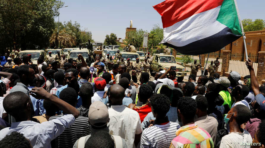 Sudanese demonstrators chant slogans in front of security forces during a protest in Khartoum, Sudan, Apr. 15, 2019.