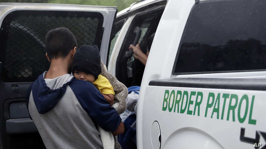FILE - Families who crossed the nearby U.S.-Mexico border near McAllen, Texas, are placed in a Border Patrol vehicle, March 14, 2019. U.S. border authorities have increased the biometric data they take from children 13 and younger.