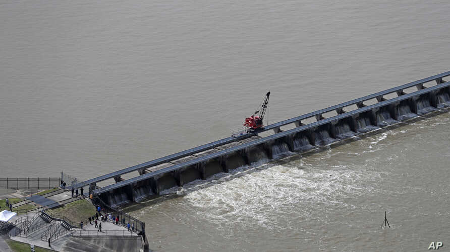 FILE - Workers open the gates of the Bonnet Carre spillway, a river diversion structure, which diverts water from the rising Mississippi River, left, to Lake Pontchartrain, in Norco, La., March 8, 2018.