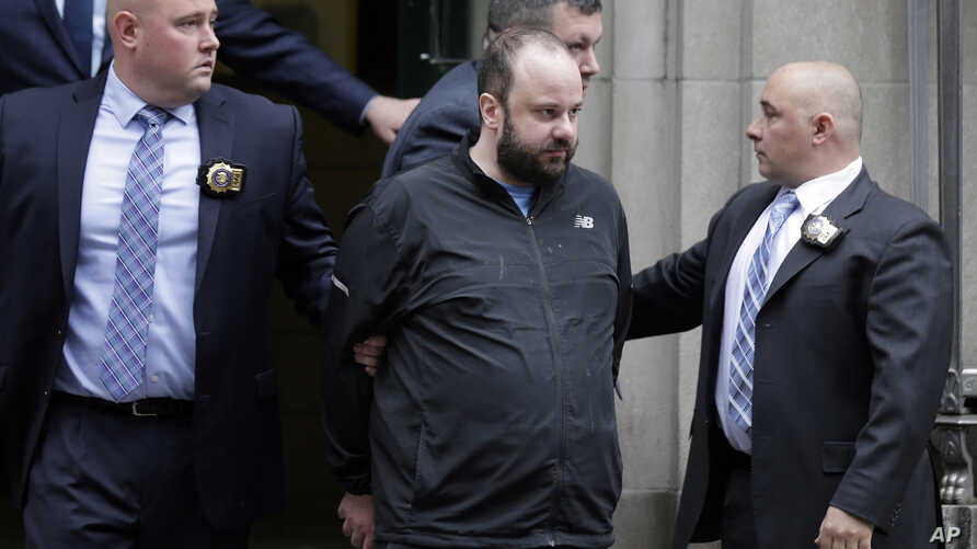 Marc Lamparello, 37, center, is escorted out of a police precinct in New York, April 18, 2019.