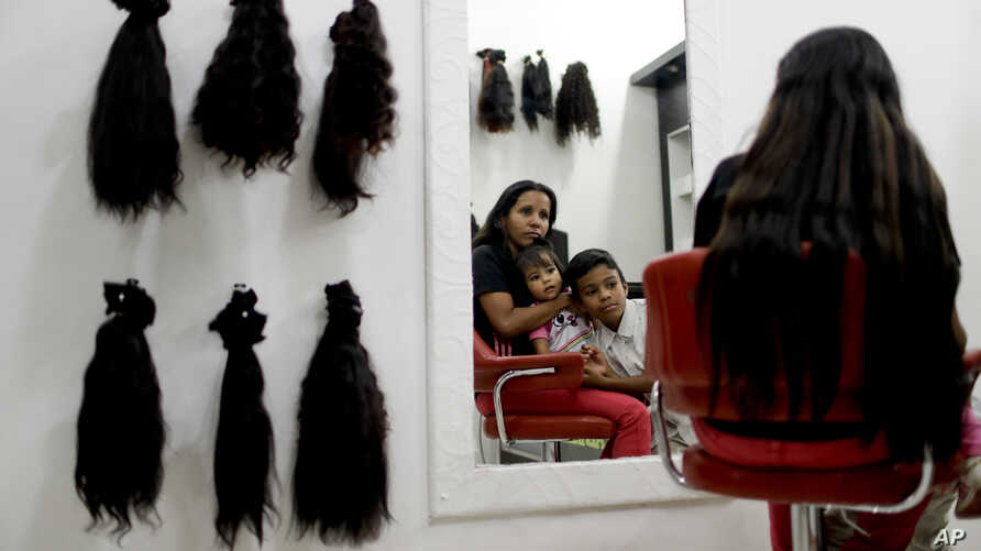 Nelly Navarro sits with her kids in a beauty salon where she came to consult how much money she could get for her hair, in Caracas, Venezuela, April 2, 2019.