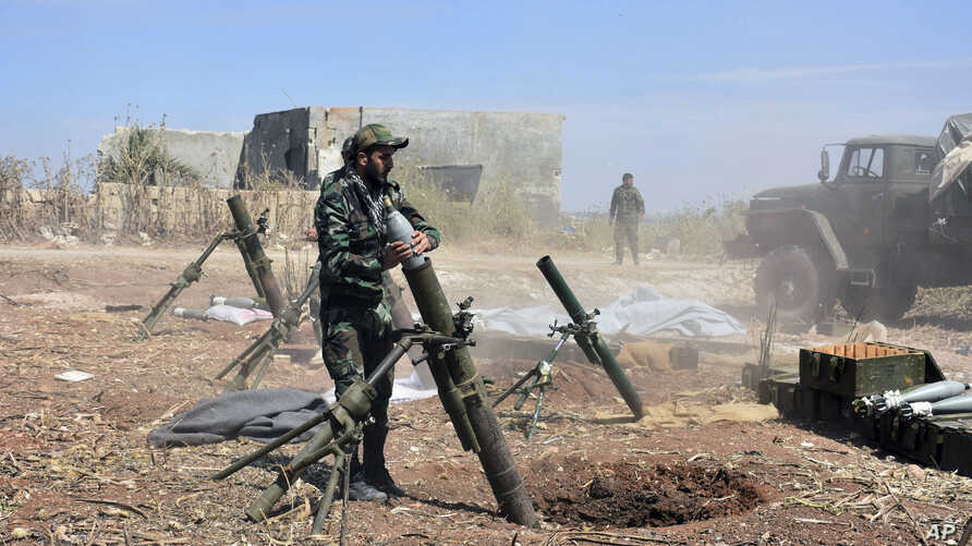 In this photo released by the Syrian official news agency SANA, Syrian army soldiers prepare to launch a mortar towards insurgents in the village of Kfar Nabuda, in the countryside of Syria's Hama province, May 11, 2019.