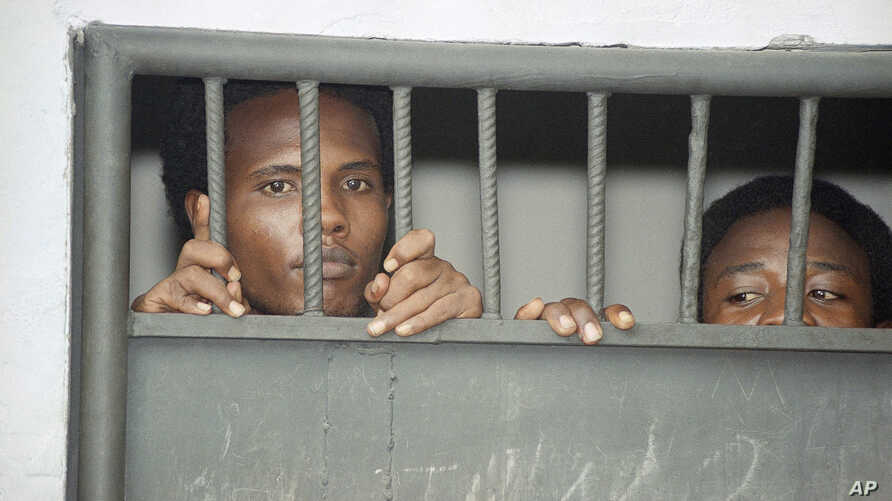 Two prisoners peer through the bars of their cell in Mogadishu on Friday, Jan. 29, 1993 at the former Criminal Investigation Division, the department that probed so-called political crimes.