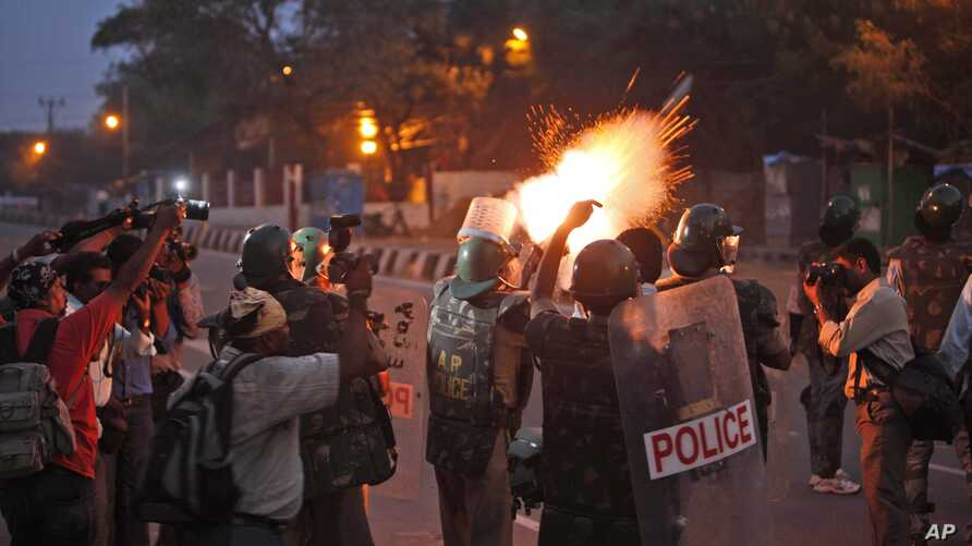 FILE - Indian police fire tear gas shells during a procession carrying the dead body of university student B. Santhosh at Osmania University in Hyderabad, India, Wednesday, Nov.7, 2012.