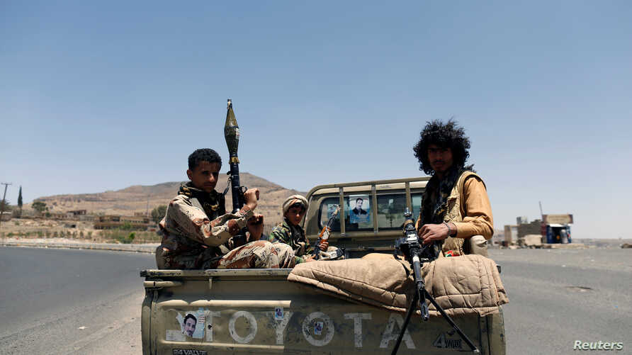 FILE - Houthi fighters ride on the back of a pickup truck on a road between the port city of Hodeida and capital Sanaa, Yemen, April 19, 2017.
