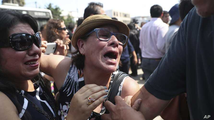 Supporters of former Peruvian President Alan Garcia cry as they learn that the former leader died from a self-inflicted gun shot, outside the hospital where he was taken after he shot himself, in Lima, Peru, April 17, 2019.