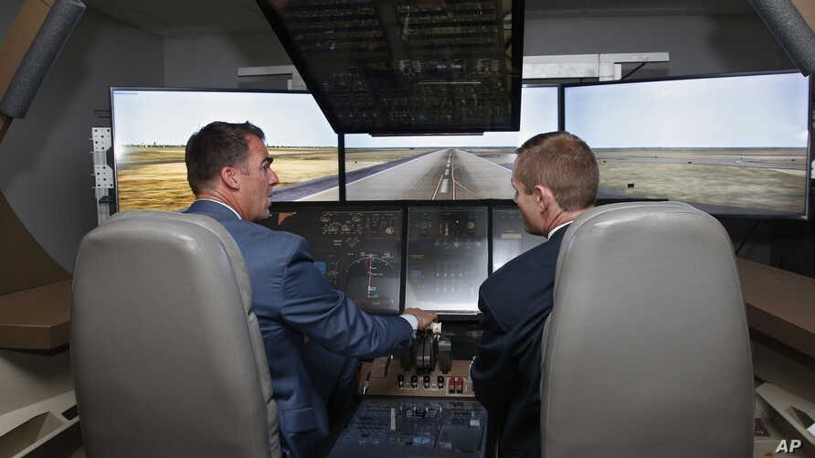 Oklahoma Gov. Kevin Stitt, left, tries his hand at a 747 flight simulator under the eye of Shawn Lynch, right, chief flight instructor, at the Oklahoma City facility of The Boeing Company, May 14, 2019, in Oklahoma City.