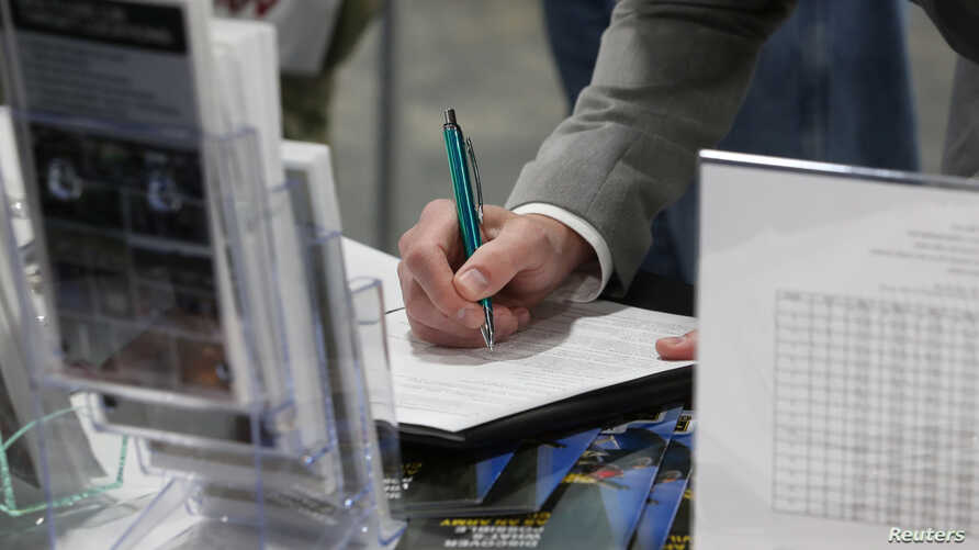 FILE - A veteran fills out a form at a military job fair in Sandy, Utah, U.S., March 26, 2019.