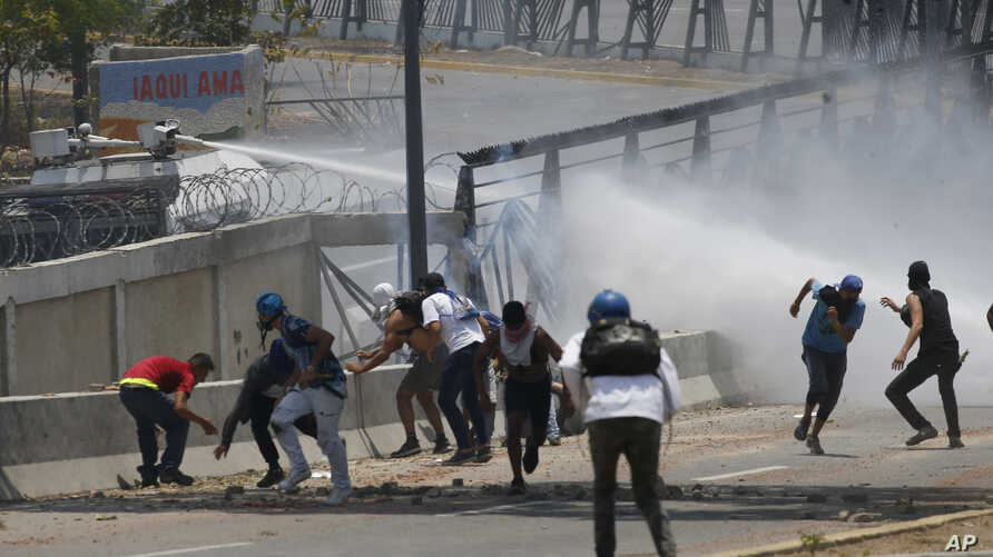 Anti-government protesters are sprayed with a water canon by security forces behind the perimeter wall of La Carlota airbase in Caracas, Venezuela, May 1, 2019.
