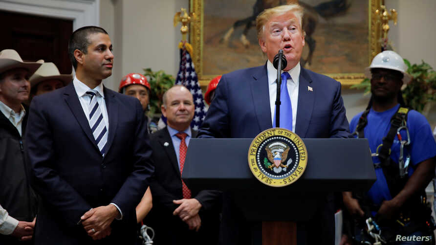 U.S. President Donald Trump speaks next to Federal Communications Commission (FCC) Commissioner Ajit Pai during an event on United States 5G deployment in the Roosevelt Room of the White House in Washington, April 12, 2019.