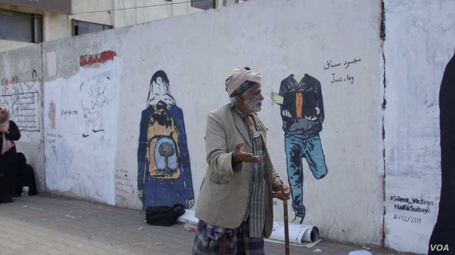 A bypasser looks at graffiti works by Yemeni artist Haifa Subay in Sanaa. The murals depict different facets of the conflict in Yemen, such as land mines and demand for girls' education.