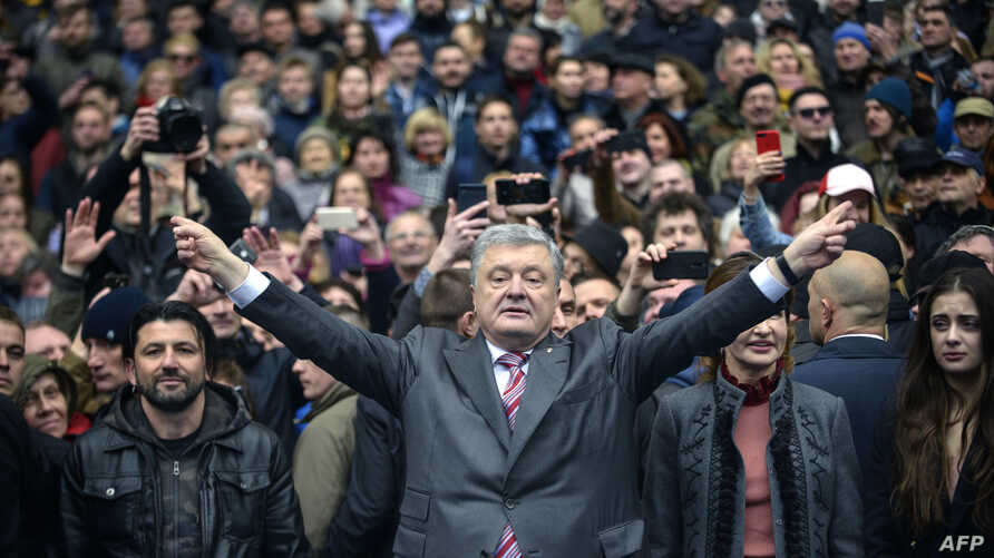 Ukrainian President Petro Poroshenko (C) gestures in front of his supporters as he waits for presidential candidate Volodymyr Zelensky for a debate before a high-stakes run-off vote at Olympiysky Stadium in Kiev on April 14, 2019.