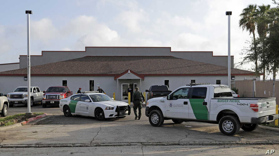 FILE - A U.S. Border Patrol Agent walks between vehicles outside the Central Processing Center in McAllen, Texas, June 23, 2018.