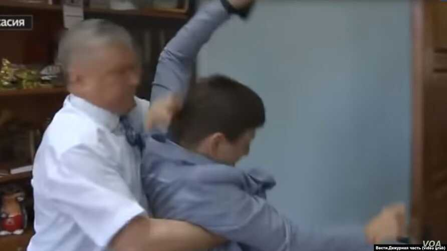 In an image taken from a video, Sergei Zaitsev, head of the Shirinsky region of Russia's Republic of Khakasia, appears to grab journalist Ivan Litoman, May 22, 2019.